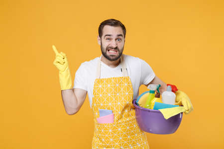 Confused man househusband in apron rubber gloves hold basin with detergent bottles washing cleansers doing housework isolated on yellow background. Housekeeping concept. Point index finger aside up.