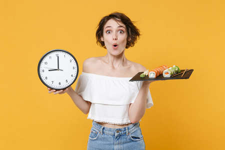 Young fun woman girl in casual clothes hold in hand clock makizushi sushi roll served on black plate traditional japanese food isolated on yellow background studio portrait. People lifestyle concept.