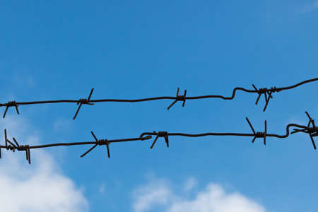 Barbed wire on the background of the free blue sky