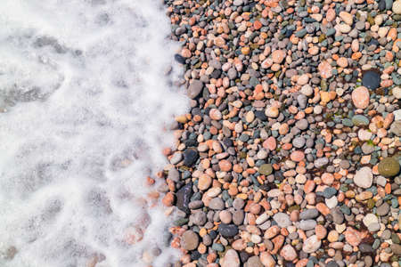 Sea wave on a pebbly beach, sea foam Stock Photo