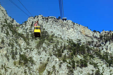Cable car to mount Ai-Petri, view from the cabin funicular to the mountain top and descending yellow booth