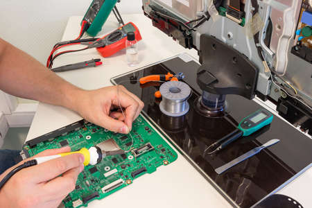 TV repair in the service center, engineer soldering electronic components 報道画像