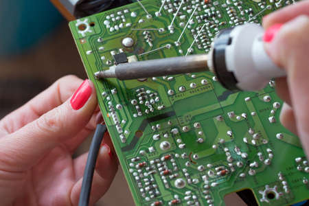 The girl-engineer repairs a switching power supply. Installation and soldering of electronic components using a soldering iron with a ceramic heater.