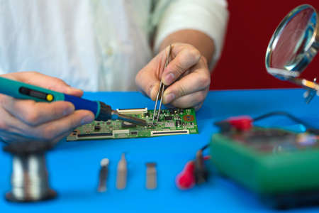 Repair of the video converter board of the TV signal. Soldering of electronic components by an engineer for the modern TVs close-up. Stock Photo