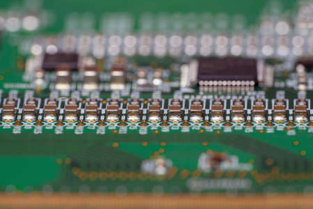 Printed circuit board with SMD capacitors close-up. Macro photography of a fragment of the decoder panel tft LCD monitor with installed electronic components. Stock Photo
