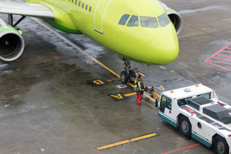 Towing the green aircraft from the runway to the Parking lot with the help of special equipment.