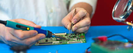 Repair PCB. Soldering of electronic components by an engineer.