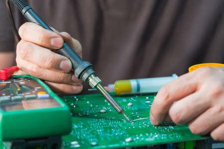 Réparation et restauration du PCB d'un bloc d'alimentation sans coupure, soudure de composants électroniques