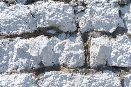 Wall of white limestone cobblestones. Natural materials in construction