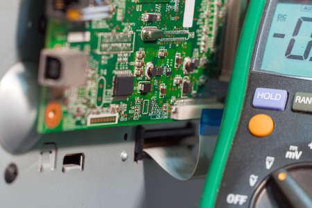 Printer motherboard and multimeter. Repair of office equipment.