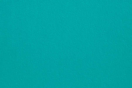Plastered concrete wall, painted in emerald color, surface texture in high resolution.