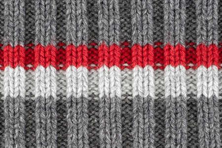 Pattern by gray, red and white knitting wool yarn texture, kraft handmade Foto de archivo