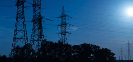 High-voltage power lines in the light of the rays of the setting sun, transporting electricity over long distances