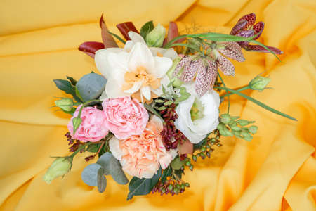 Chic mini bouquet of roses, daffodils and other flowers on a yellow background