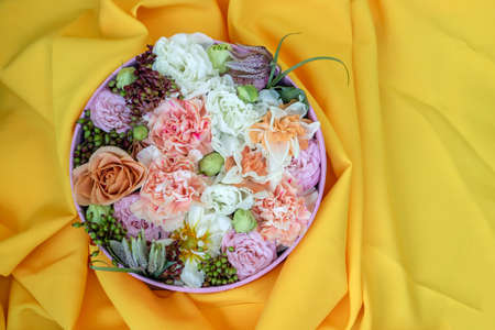 Bouquet of roses, daffodils, eustoma and other flowers on a yellow background. The idea of a floral arrangement in a round box