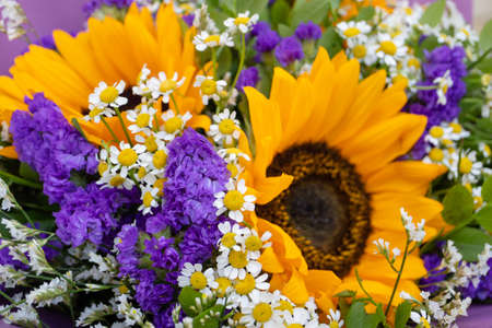 Flower arrangement, a bouquet with sunflowers and field daisies