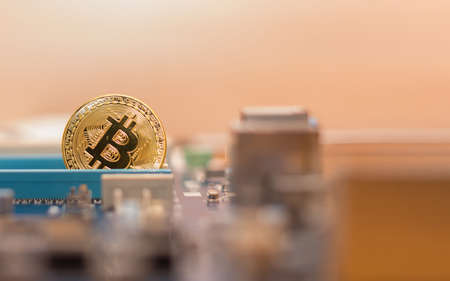 Bitcoin cryptocurrency on the background of a computer motherboard Stock Photo