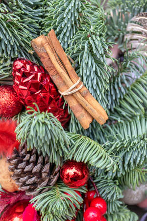 New Year and Christmas decoration with cinnamon sticks, cone and red ball. Vertical photo