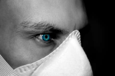 Preventive protection against viruses. Portrait of a man with bright eyes in a medical mask