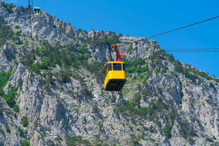 Cable car rope road on Ai-Petri mountain. Yellow cabin of Cableway.