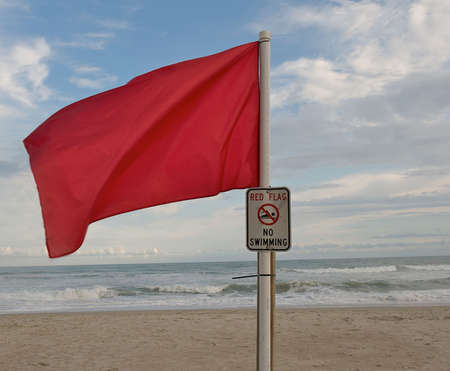 Red warning flag flying at the beach to warn swimmers of danger. Stock Photo