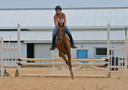Athletic teen girl jumping a horse over rails. Stock Photo
