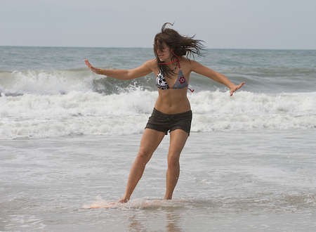 Teen girl skim boarding in the surf on the beach at Emerald Isle, North Carolina.