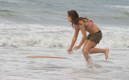 Teen girl throwing a skimboard into the surf at Emerald Isle, North Carolina.