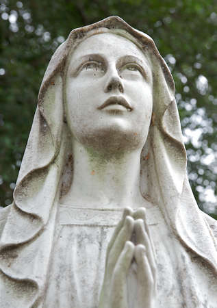 Ancient cemetary heastone of a woman in prayer looking toward heaven.  Spider webs cover the eyes giving the image a spooky and creepy feeling. Stock Photo