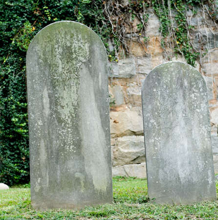 Two ancient headstones in a cemetery.  The aging of the stone has worn away any words that may have once been present.