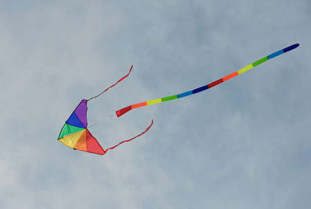 Colorful rainbow kite flying high in the sky.