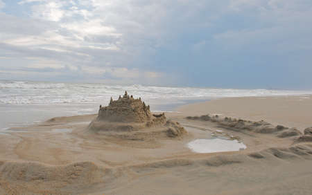Sand castle surrounded by  a moat in a beautiful beach image. Stock Photo