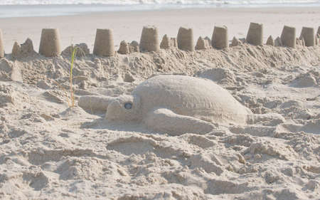 Sand sculpture of a sea turtle protected from the surf by a fort.