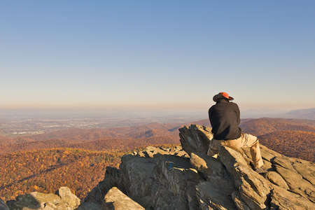 Man reflecting life while sitting on Humpback Rock in the Blue Ridge Mountains of Virgina.  The hike to this scenic overlook is about 1 mile straight up, an acheivement for any hiker.  Room for text at the top of the image. photo