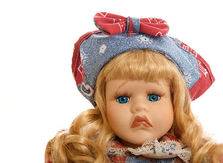 Portrait of a frowning porcelain doll isolated on white. Stock Photo