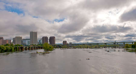 Richmond Virginia city skyline as viewed from the Belle Isle bridge.  Beautiful cloudfilled sky hovering over the James River.