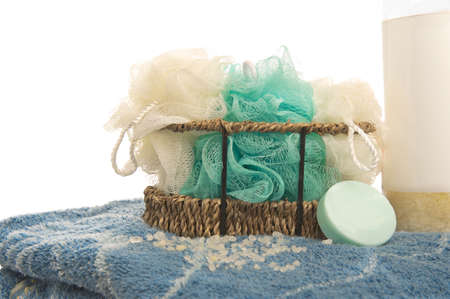 pouf: Isolated shower pouf sponges in a basket, sitting on a towel with soap and bath salts.