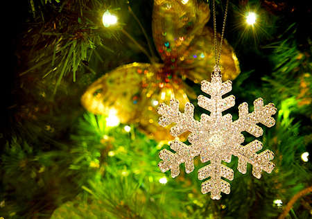 Snowflake ornament hanging from a Christmas tree. Stock Photo