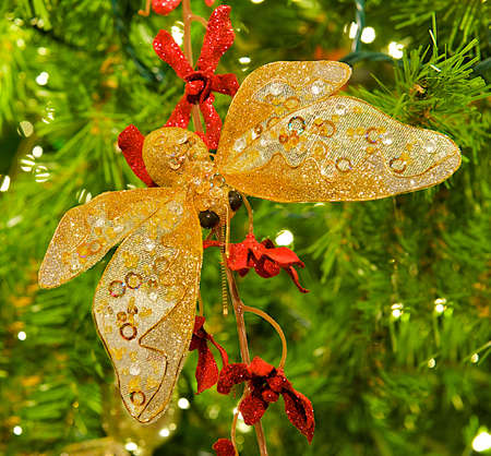 Butterfly Christmas tree ornament haning from a beautifully lit tree. Stok Fotoğraf