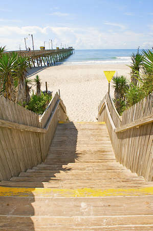 Stairs leading to a beautiful beach showing the pier and ocean in the background.