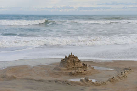 Sand castle surrounded by a moat on the beach.  Ocean and cloud filled sky in the background. Zdjęcie Seryjne