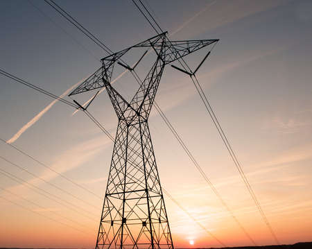 high voltage: Electric power pylon and wires silhouetted by a colorful sunset.