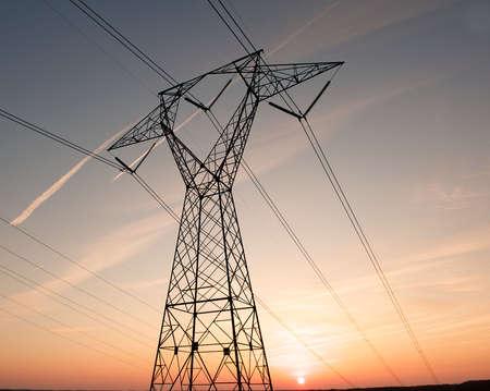 hoogspanningsmasten: Elektrische stroom pyloon en draden afgetekend door een kleurrijke zons ondergang.