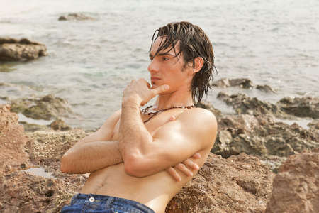 Young man resting thoughtfully on the rocks in the ocean, his hair wet from a recent swim.