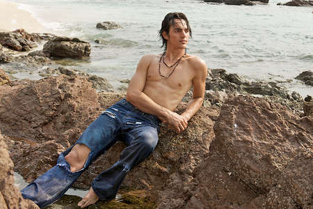 Muscular young man laying on the rocks on the beach looking toward the sunlit water pensively.