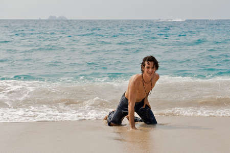 Athletic young man on the beach preparing to stand up after swimming in the ocean waves. photo