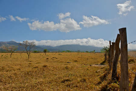 Pasture during the dry season in Guanacaste province of Costa Rica.  Beautiful blue cloud filled sky covers the mountains. Stock Photo