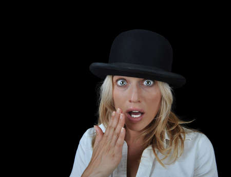 Beautiful surprised blonde woman wearing a hat on a black background with room for text. Stock Photo