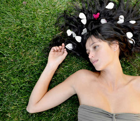Beautiful brunette model laying in the grass. photo