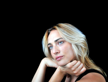 Beautiful pensive woman on black background. Stock Photo